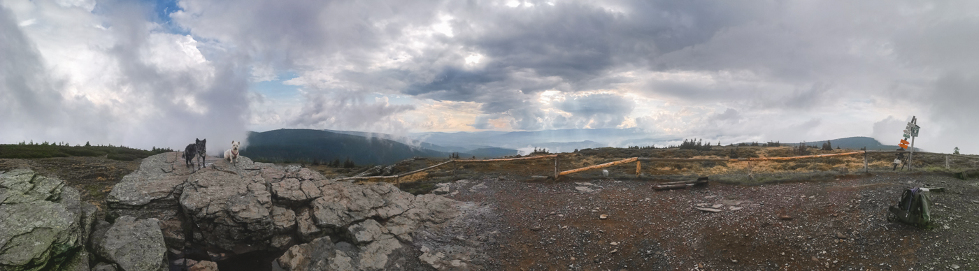 Panorama z góry Keprnik w Czechach. Na pierwszym planie formacje skalne, Fibi i Krakers. W tle górski pejzaż rozciągający się aż po horyzont. Mieszane chmury, jedne zwiastują deszcz, przez inne przebija się słońce i błękit nieba.